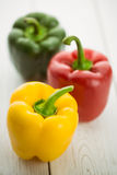 Three peppers on chopping board Royalty Free Stock Photos