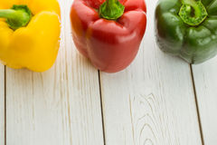 Three peppers on chopping board Royalty Free Stock Images