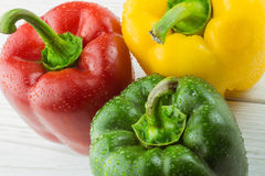 Three peppers on chopping board Royalty Free Stock Photo