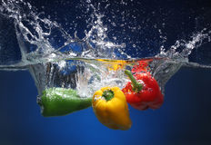 Three peppers falling into water Royalty Free Stock Images