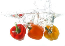 Three peppers falling in water Stock Photos