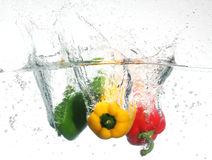Three peppers falling into water, over white Stock Photos