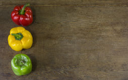 Three peppers. Three multi-colored pepper on a wooden background royalty free stock images