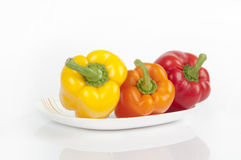 Three peppers on a plate. Red yellow orange Stock Images