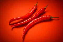 Three peppers on a red background Stock Photos