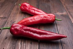Three peppers on wooden background. royalty free stock image