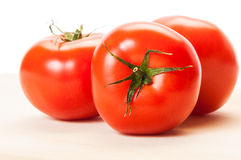Three perfect red tomatoes on a wooden board Royalty Free Stock Photography