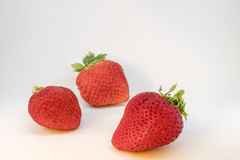 Three perfectly cleaned strawberries with leaves isolated on the white background Royalty Free Stock Photos