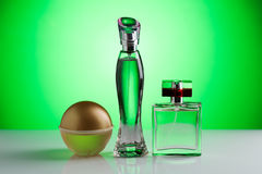 Three perfume bottle on a bright green background Royalty Free Stock Photo