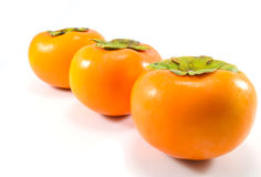 Three Persimmon. Three ripe persimmon standing in a row Stock Photos