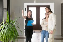 Real agent showing property for sale to young married couple stock images