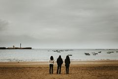 Three Person Standing Near the Seashore stock photography
