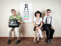Three person wearing spectacles in an office at the doctor Royalty Free Stock Image