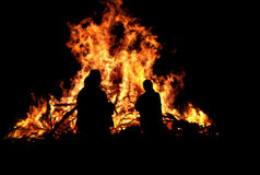 Three persons in front of bonfire royalty free stock photography