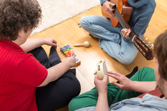 Three persons playing sundry instruments. At home Royalty Free Stock Photography