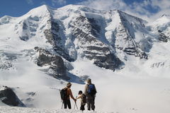 Three persons are watching on Swiss mountains Royalty Free Stock Image