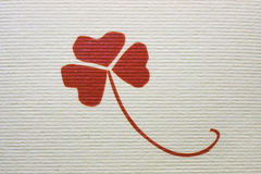 Three petals of clovers, a graceful plant with a long curved arch, a painted image of a red color, on rough paper with striped rel. Three petals of clovers, a Royalty Free Stock Photos