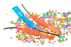 Three petards on background of colorful confetti. Royalty Free Stock Photos