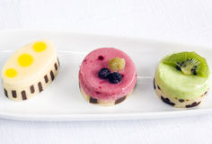 Three petit fours. Lemon, red fruits and kiwi. Main focus on red fruits one Royalty Free Stock Photography