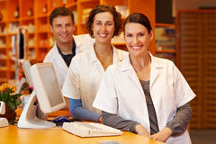 Three pharmacists at counter. Three pharmacists at a counter in a pharmacy Stock Photography
