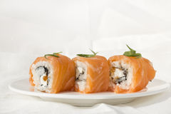Three Philadelphia rolls. 3 Philadelphia rolls on white plate with cloth linen background Stock Image