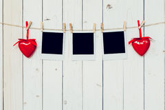 Three photo frame blank and red heart hanging on white wood back Stock Images