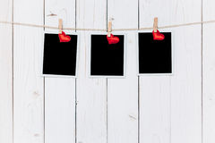 Three photo frame blank and red heart hanging on white wood background with space Royalty Free Stock Image