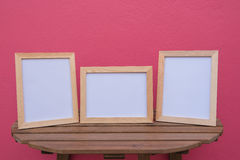 Three photo Frame on a wooden on pink background . Royalty Free Stock Photo
