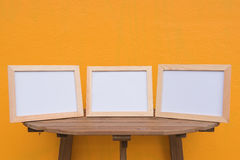 Three photo Frame on a wooden on Yellow background . Stock Photo