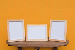 Three photo Frame on a wooden on Yellow background . Royalty Free Stock Photos