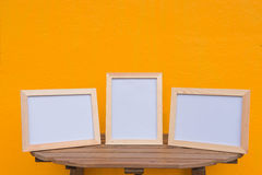 Three photo Frame on a wooden on Yellow background . Stock Photos