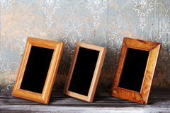 Three photo-frames on old table Stock Photography