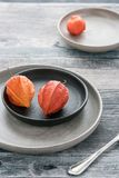 Two physalis on a rustic background, old-fashioned fork royalty free stock images