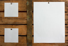 Three pieces of blank paper. Tacked to wooden background.Ready for your text Royalty Free Stock Photo