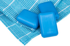 Three pieces of blue soap on checkered towel on white. Three pieces of blue soap on checkered towel isolated on white background Royalty Free Stock Photos