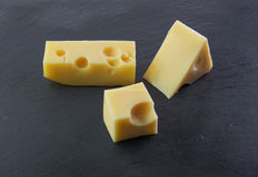Three pieces of cheese. On a black stone slate plate Royalty Free Stock Photos