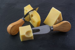 Three pieces of cheese. On a black stone slate plate with knife and fork royalty free stock image