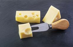 Three pieces of cheese. On a black stone slate plate stock images