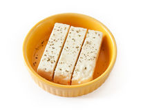 Three pieces of feta cheese on a yellow plate. Stock Images