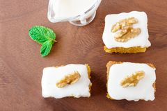 Three Pieces of homemade carrot cake with icing cream on wooden plate. Stock Photo