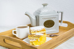 Three pieces of lemon pie with slice of lemon and cup of tea Stock Photo