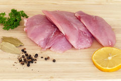 Three pieces of raw turkey steak with spices on a wooden board Royalty Free Stock Photos