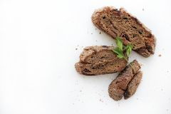 Three pieces of rye bread and a sprig of parsley on a white background. stock image