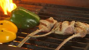 Three pieces of steak on the bone and two halves of peppers grilled, from the grilled coals there is a flame, a dish in. The restaurant, fried vegetables stock footage