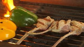 Three pieces of steak on the bone and two halves of peppers grilled, from the grilled coals there is a flame, a dish in. The restaurant, fried vegetables stock video footage