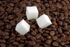 Three pieces of sugar against coffee grains Stock Images