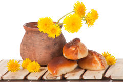 Three pies and dandelions in  clay pot Royalty Free Stock Images