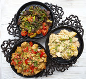 Three pig-iron frying pans with hot tasty food on a white wooden Royalty Free Stock Images