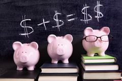 Three Piggy Banks with savings investment growth plan. Three pink piggy banks standing on books next to a blackboard with simple money math.  Sharp focus on the Royalty Free Stock Image