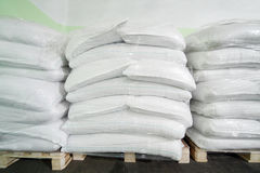 Three piles of big white sacks at large warehouse Stock Photography